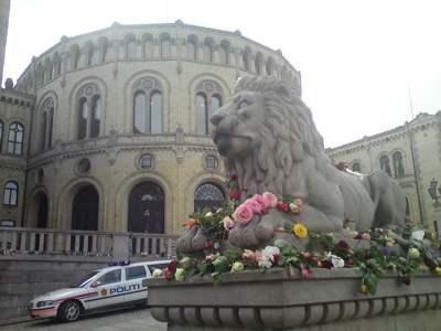 Løvefigur med blomar framfor Stortinget